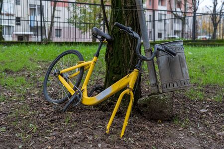 Yellow bicycle deposited out of the containers, urban pollution.