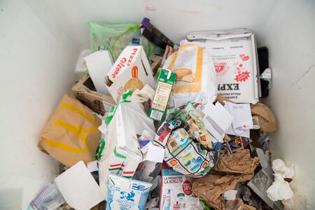Milan, Italy - December 02, 2019: selective waste collection bins, big white dumpster full of garbage paper