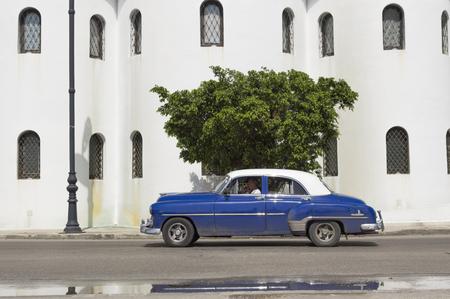 ortodox: Blue car running in Havana in front of the russian ortodox church