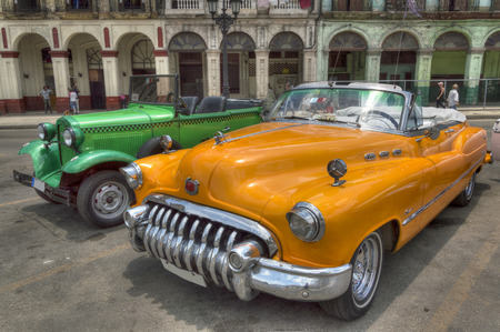 Orange and green old american cars in front of Capitolio, Havana, Cuba