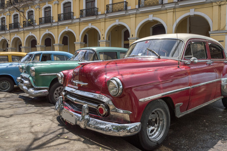 colonial building: HAVANA, CUBA - MAY 28, 2014: A series of classic cars in front of a colonial building