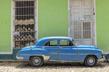 coche antiguo: Coche cl�sico azul delante de una tienda de recuerdos en Trinidad, Cuba Editorial