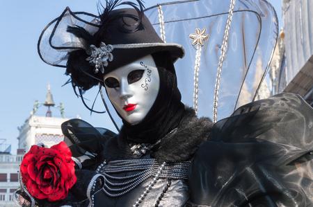 mascara de carnaval: señora vestida negro con una rosa roja Durante el carnaval de Venecia