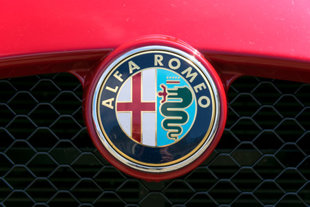 car grill: TURIN, ITALY - JUNE 9, 2016: Alfa Romeo logo on the grill of a red car model Editorial
