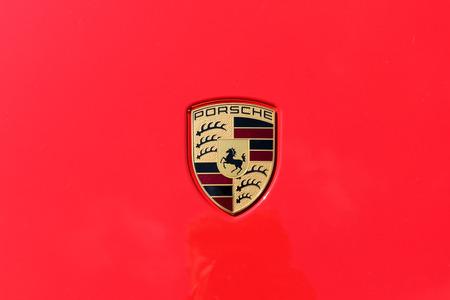 TURÍN, ITALIA - 9 junio, 2016: insignia del coche de Porsche sobre un fondo rojo Foto de archivo - 58569785