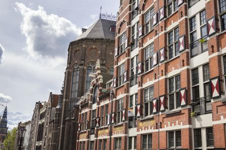 Colorido típico edificio holandés y Iglesia de San Nicolás en Amsterdam, Países Bajos Foto de archivo - 65675692