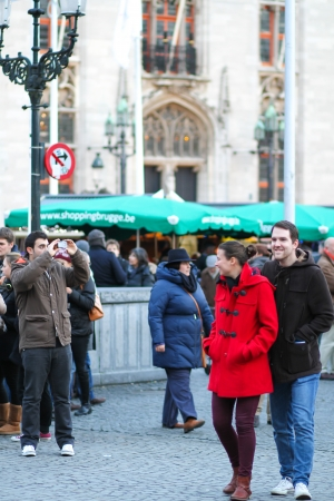 Bruges, Belgium - December 28, 2013 People are walking across the market place of Bruges on a cold winter day  Editorial