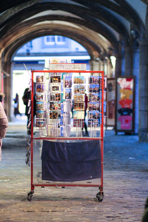 Bruges, Belgium - December 28, 2013 People are walking by a postcards stand under an arch of a street in Bruges