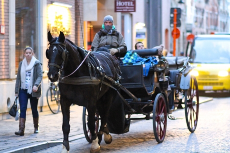 Bruges, Belgium - December 28, 2013 People are enjoying a horse carriage ride in the streets of Bruges