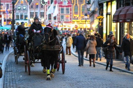 Bruges, Belgium - December 28, 2013 A couple of horse carriages are leaving the market square of Bruges  The square is busy with tourist and nicely decorated during December before Christmas