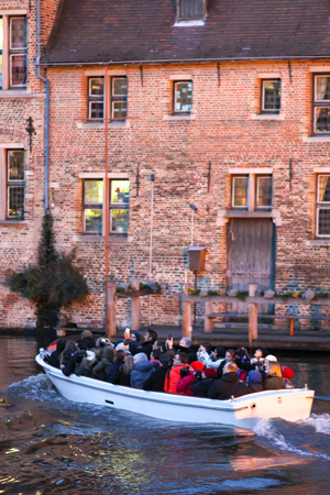 Bruges, Belgium - December 28, 2013 Tourists are enjoying sightseeing on a boat in Bruges