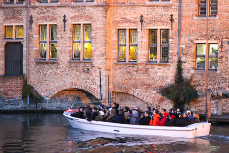 Bruges, Belgium - December 28, 2013 Tourists are enjoying sightseeing on a boat in Bruges