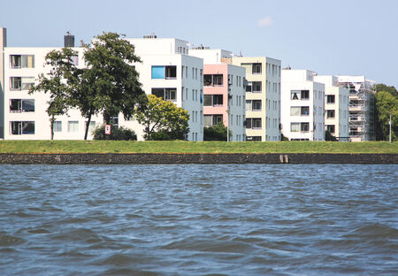 river bank: Row of modern building beside a river bank