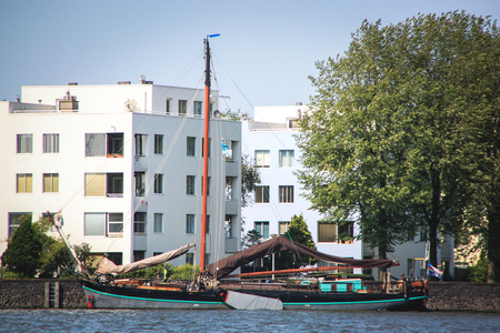 Old boat parked on a river, beside modern buildings