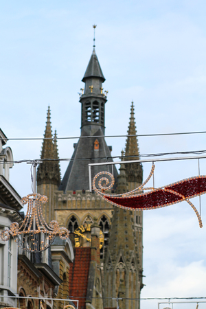 ypres: Some Christmas street decorations with the Belfry of Ypres in the background
