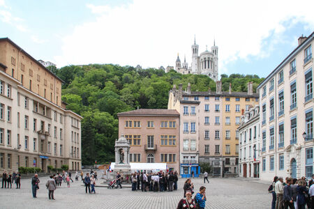 Lyon, France - May 19, 2012 Groups of tourists are following their guide on place Saint Jean in Lyon  Behind, on the top of the hill the basilica Notre Dame de Fourvière