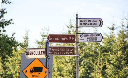 Wicklow, Ireland - August 21, 2013 A signpost beside a woodforest is indicating the direction for Glendalough and other famous places in Ireland