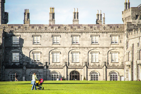 Kilkenny, Ireland - October 31, 2013 A woman with a stroller is walking by a main tourist attraction in Ireland, the Kilkenny Castle  It is a castle who was built in 1195 by William Marshal