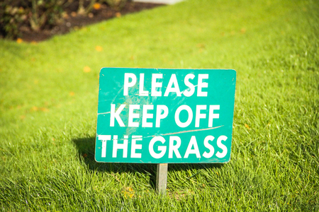 A green  Please keep off the grass  sign planted into the grass