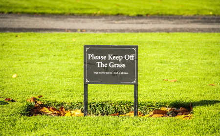 A   Please Keep Off The Grass  sign with leaves around  Stock Photo