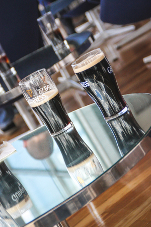 Few pints of Guinness on a glass table Editorial