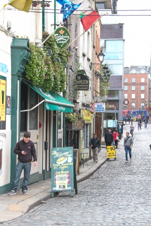 Dublin, Ireland - October 24, 2013 A man is checking is mobile phone on the sidewalk of Fownes Street in Temple Bar