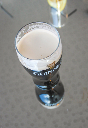 A pint of Guinness on a glass table