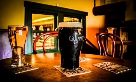 cerveza negra: Una pinta de Guinness en una mesa en un pub