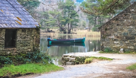 Small fishing boat on a lake between two cottages