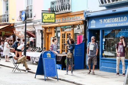 London, United Kingdom - July 24, 2013 People are walking out of an antiques gallery on the Portobello Road in Notting Hill district located in west London
