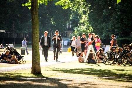 London, United Kingdom - July 24, 2013 People are enjoying a sunny day in Portman Square, London  Two business men are walking through the park