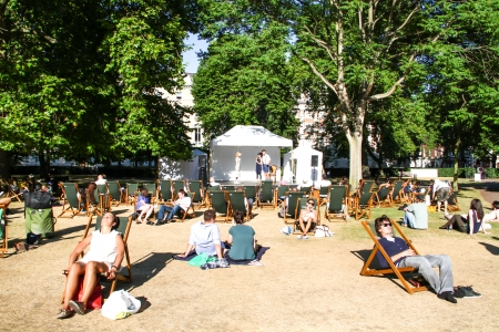 London, United Kingdom - July 24, 2013 People are  watching three comedians performing on a stage in Portman Square, London