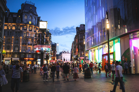London, United Kingdom - July 24, 2013 People walking at Leicester Square et night  A the background we can see a part of the Piccadilly Circus