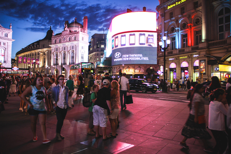 London, United Kingdom - July 24, 2013 Tourists enjoying an evening walk at Piccadilly Circus