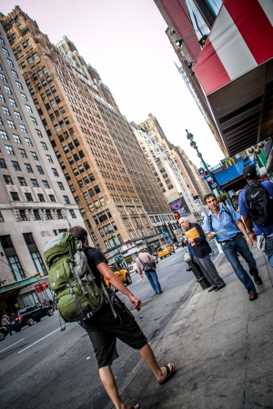 New York City, USA - August 7, 2012 A backpacker is wamlking on the sidewalk of the 8th Avenue in New York City