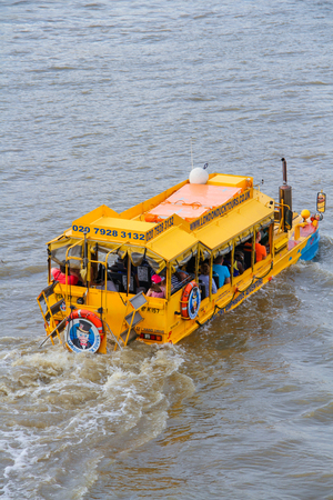 London, United Kingdom - July 26, 2013 A London Duck Tour amphibious vehicle full of tourists, passing the Houses of parliament on the Thames River