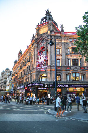 London, United Kingdom - July 24, 2013 A couple is crossing a street near Leicester Square to join a crowded sidewalk along the Hippodrome Casino  Editorial