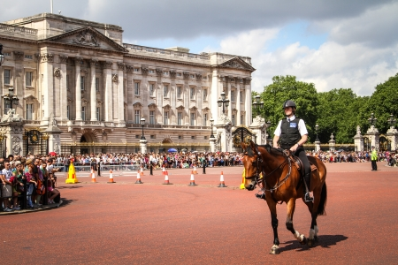 London, United Kingdom - July 28, 2013 Mounted police woman near Buckingham Palace surrounded by tourists  Editorial