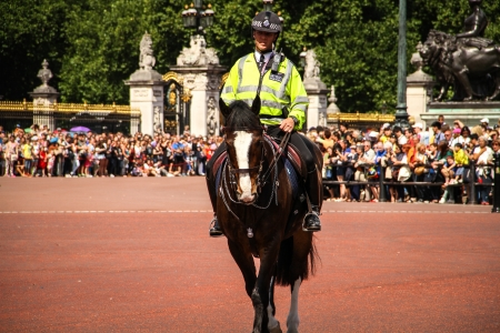 London, United Kingdom - July 28, 2013 Mounted police man beside the Victoria Memorial and the Buckingham Palace