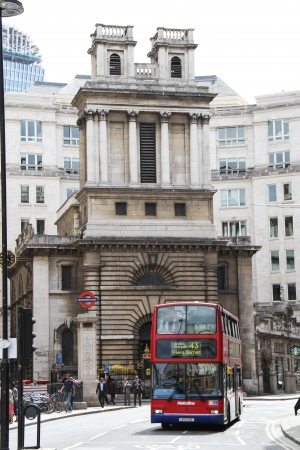 London, United Kingdom - July 26, 2013 A red bus is driving by the Saint Mary Woolnoth Church of England