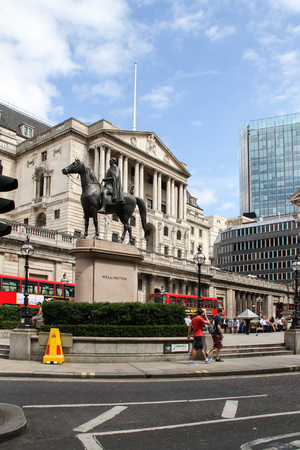 London, United Kingdom - July 26, 2013 Two people are walking by the Wellington statue  near the Bank of England