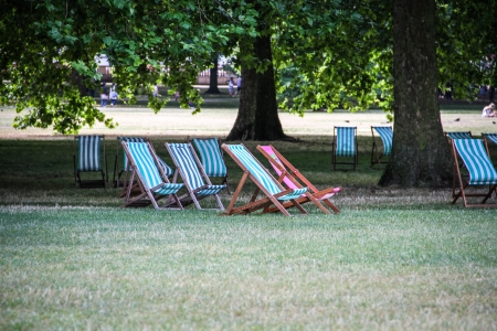 Folding wooden deckchairs for hire in a park, London