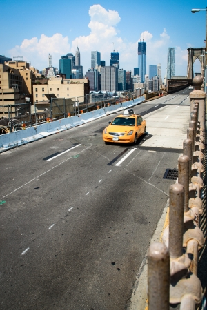 A yellow cab is leaving the Brooklyn Bridge  Stock Photo