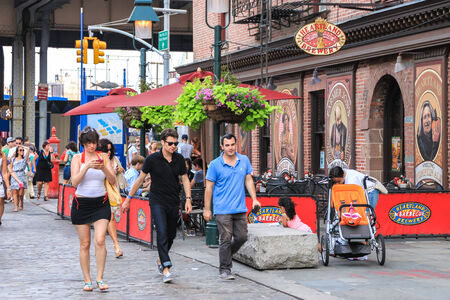 New York, USA - August 11, 2012 , 2012 People are walking, on a paved street, by a brewery located on Fulton Street near Pier 17