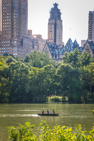 New York, USA - August 12, 2012 Three people in a small punt in the Lake of Central Park