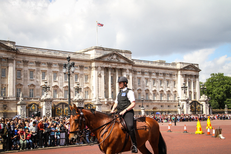London, United Kingdom - July 28, 2013 Mounted police woman near Buckingham Palace surrounded by tourists