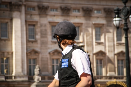 London, United Kingdom - July 28, 2013 Close up on mounted police woman with Buckingham Palace at the back