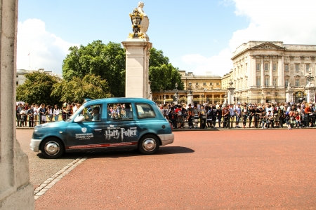 London, United Kingdom - July 28, 2013 A taxi is leaving the Buckingham Palace while tourists are waiting for the change of guards