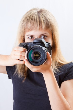 Young beautiful woman taking a photo with a digital camera  photo
