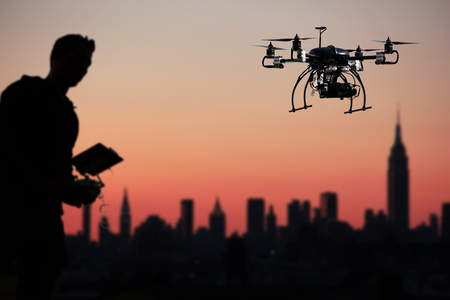pilot is flying the drone with the camera with sunset background